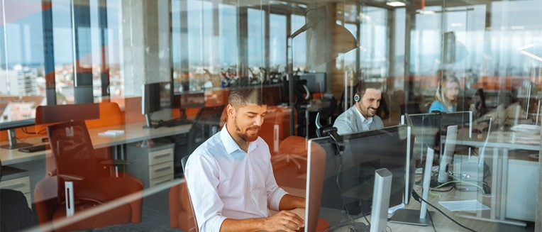 man sitting at computer behind office window