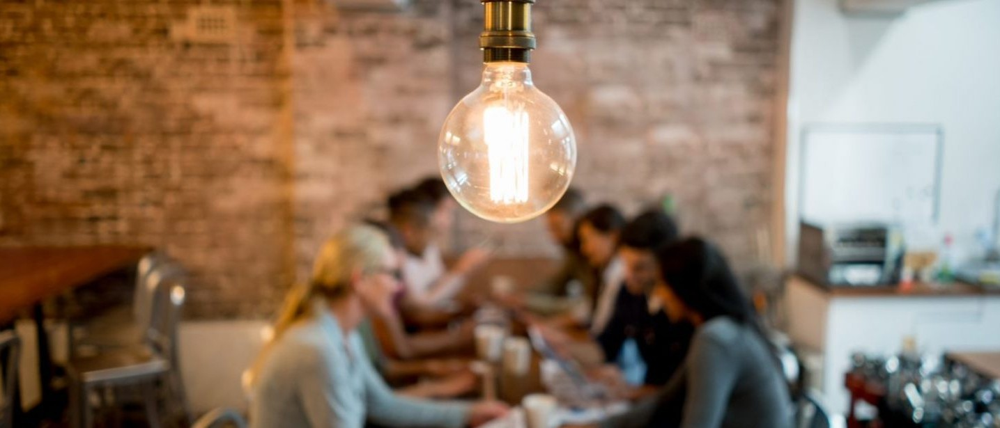 light bulb with table and people in background